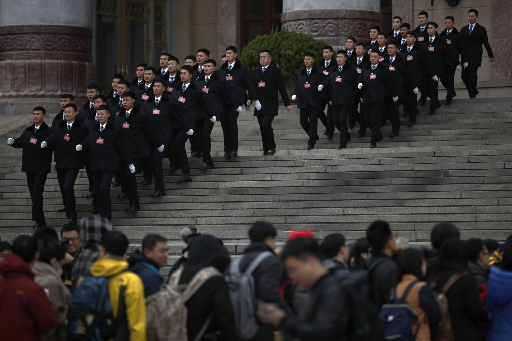 Chinese soldiers in usher uniforms march past journalists who line up to enter the Great Hall of the People for a press conference ahead of Monday's o...