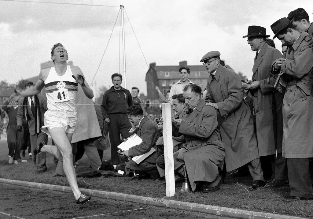 FILE - In this May 6, 1954 file photo, Britain's Roger Bannister hits the tape to become the first person to break the four-minute mile in Oxford, Eng...