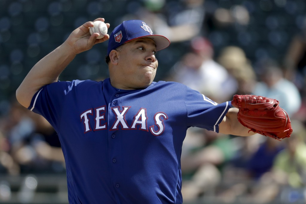 Texas Rangers starting pitcher Bartolo Colon throws against the Oakland Athletics during the first inning of a spring baseball game in Mesa, Ariz., Tu
