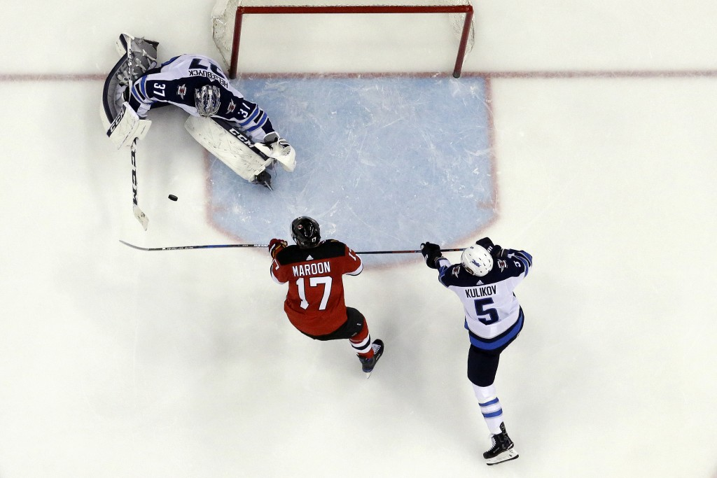 Winnipeg Jets goaltender Connor Hellebuyck, top left, deflects a shot by New Jersey Devils left wing Patrick Maroon, center, as Jets' Dmitry Kulikov,