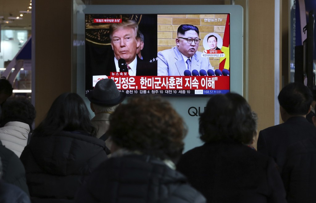 People watch a TV screen showing North Korean leader Kim Jong Un and U.S. President Donald Trump, left, at the Seoul Railway Station in Seoul, South K