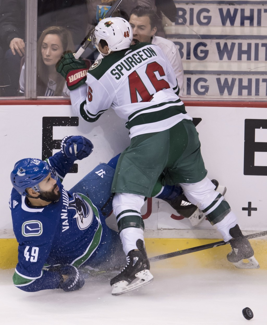 Minnesota Wild defenseman Jared Spurgeon (46) goes into the boards with Vancouver Canucks right wing Darren Archibald (49) during the second period of