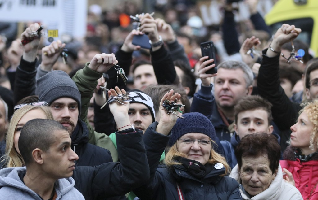 Demonstrators show their key chains during an anti-government rally in Bratislava, Slovakia, Friday, March 9, 2018. The country-wide protests demand a