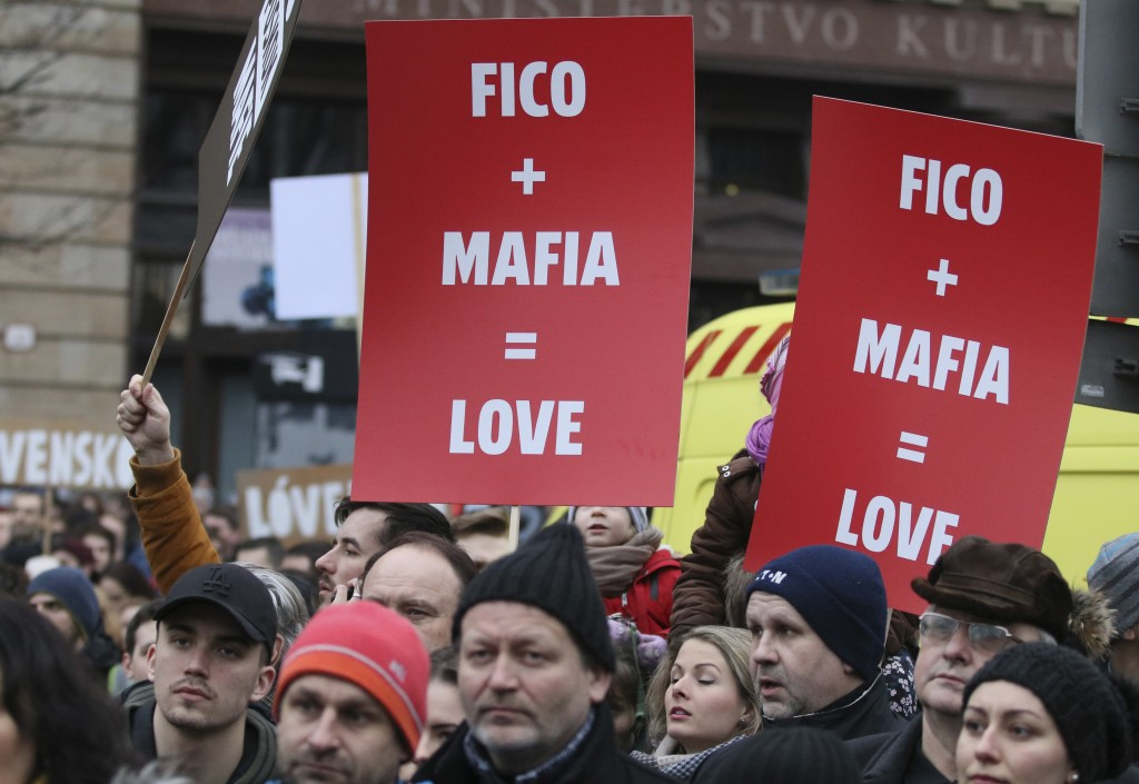 Demonstrators hold posters linking Slovakian Prime Minister Robert Fico to the mafia during an anti-government rally in Bratislava, Slovakia, Friday,