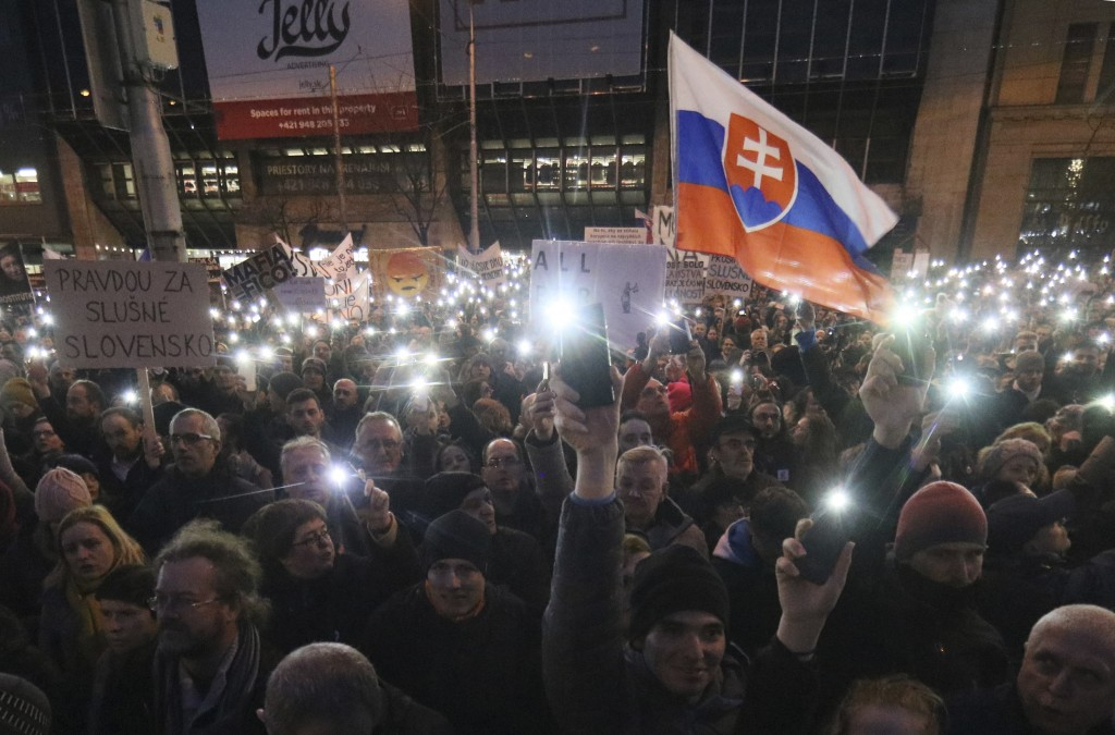 Demonstrators light with the the torches of their smartphones during an anti-government rally in Bratislava, Slovakia, Friday, March 9, 2018. The coun