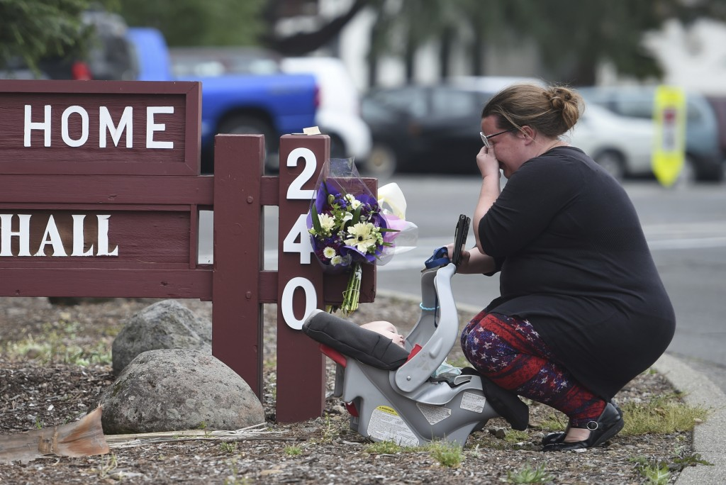 A woman, who declined to give her name, cries after placing flowers at a sign at the Veterans Home of California, the morning after a hostage situatio