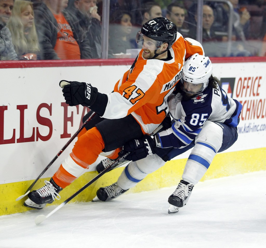 Philadelphia Flyers' Andrew MacDonald, left, and Winnipeg Jets' Mathieu Perrault vie for the puck during the first period of an NHL hockey game Saturd...