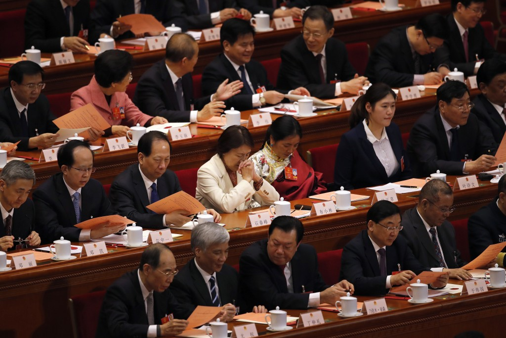 A female delegate, center, reacts as she and other delegates prepare to cast their votes for an amendment to China's constitution that will abolish te...