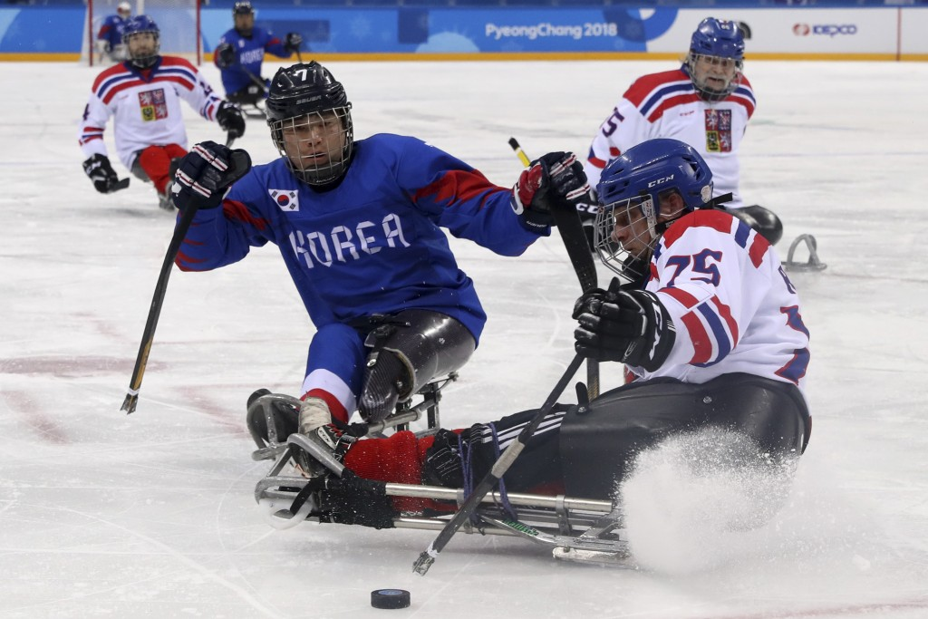 Czech Republic's Jiri Raul keeps the puck from South Korea's Choi Kwang Hyouk during a preliminary Ice Hockey match of the 2018 Winter Paralympics hel...
