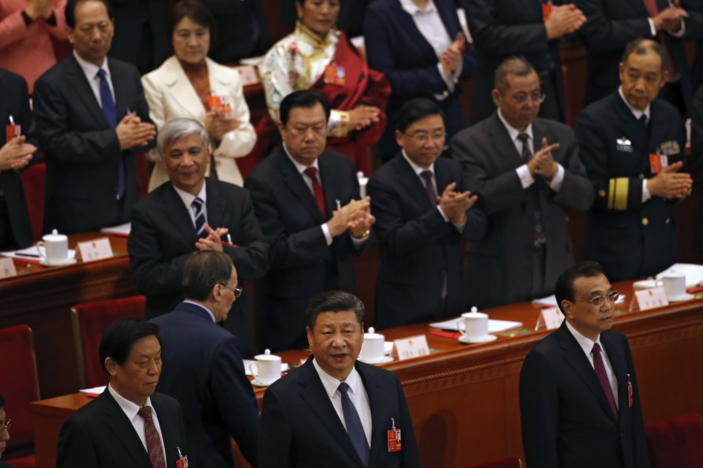 Chinese President Xi Jinping, center, looks as he and leaders arrive for a plenary session of the National People's Congress at the Great Hall of the ...