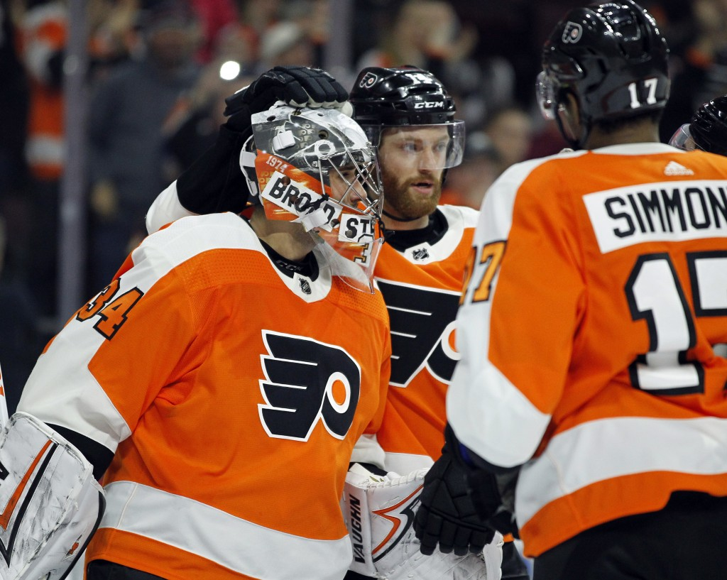 Philadelphia Flyers goalie Petr Mrazek, left, and Sean Couturier, center, celebrate the 2-1 win over the Winnipeg Jets at the end of an NHL hockey gam...