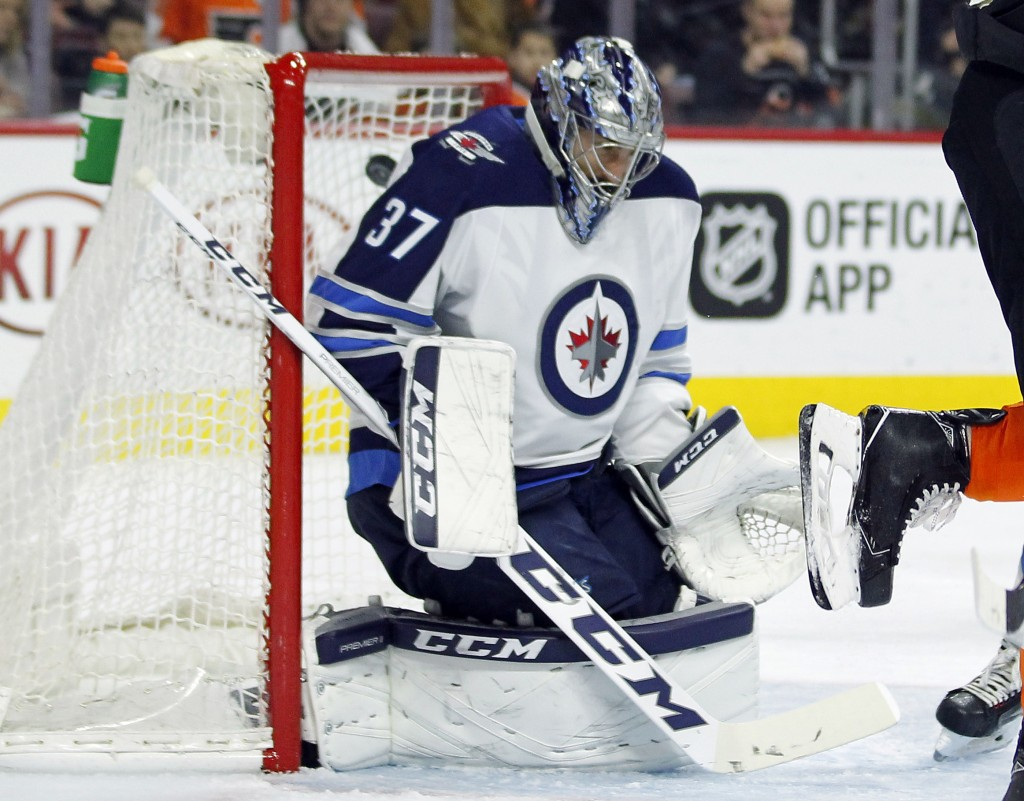 The puck gets past Winnipeg Jets goalie Connor Hellebuyck for a goal by Philadelphia Flyers' Claude Giroux during the second period of an NHL hockey g...
