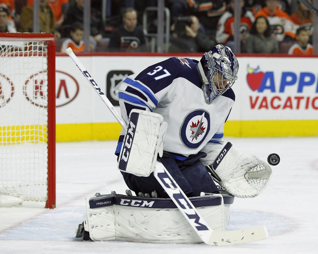 Winnipeg Jets' Connor Hellebuyck gloves a shot on goal during the second period of an NHL hockey game against the Philadelphia Flyers' Saturday, March...