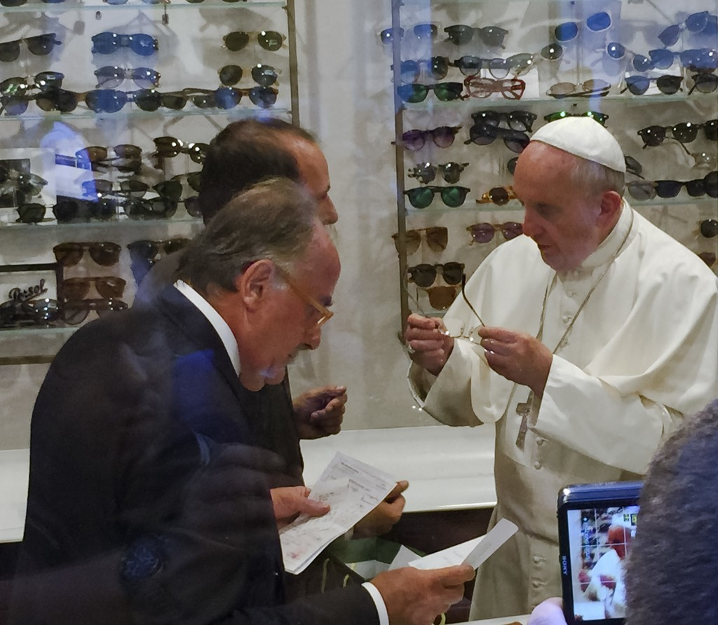 FILE - In this Sept. 3, 2015 file photo, Pope Francis tries on a pair of spectacles in an eyeglass store in via del Babuino, in central Rome. When Car