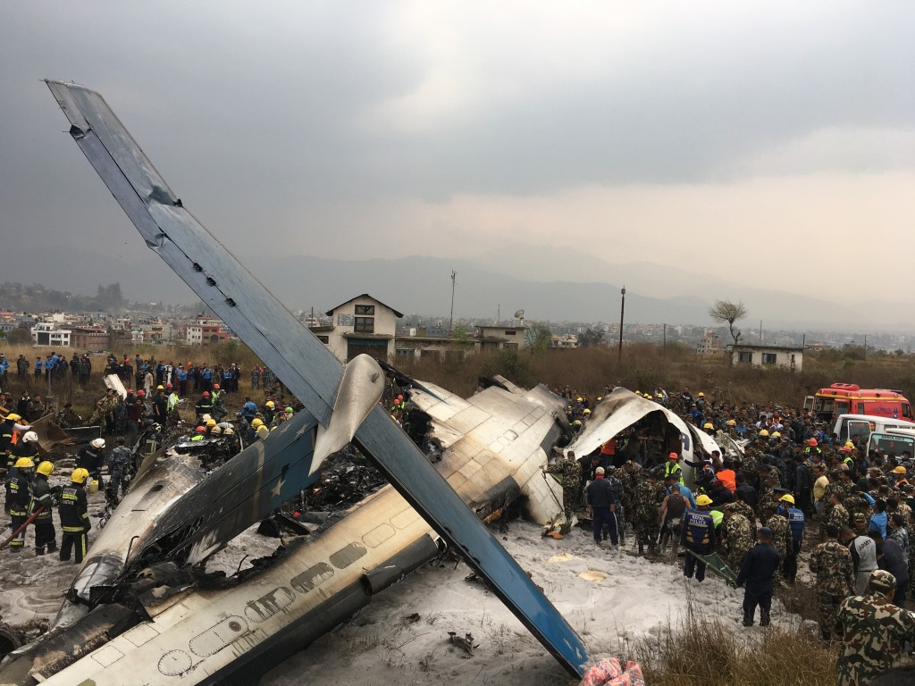 Nepalese rescuers stand near a passenger plane from Bangladesh that crashed at the airport in Kathmandu, Nepal, Monday, March 12, 2018. (AP Photo/Nira