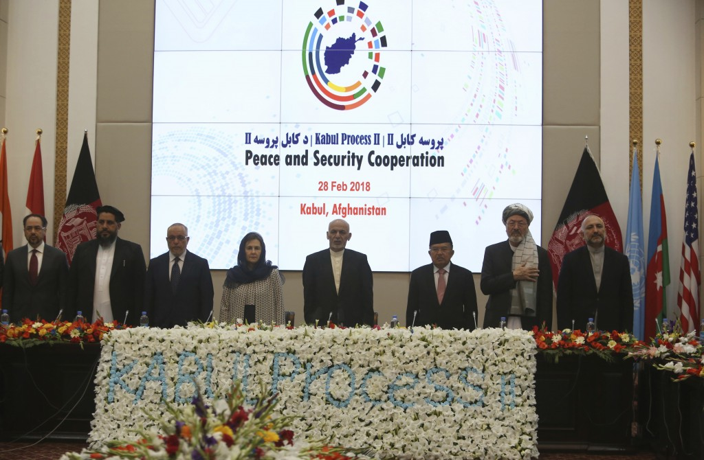 FILE - In this Wednesday, Feb. 28, 2018 file photo, Afghanistan's President Ashraf Ghani, center, and delegates stand for the national anthem during t...
