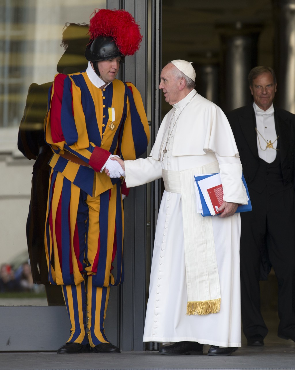 FILE - In this Oct. 16, 2015 file photo, Pope Francis shakes hands with a Vatican Swiss guard as he leaves after a morning session of the Synod of bis