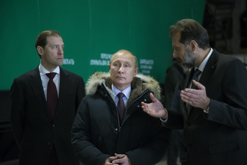 In this photo taken on Tuesday, March 6, 2018, Russian President Vladimir Putin, center, listens to Uralvagonzavod Scientific and Industrial Corporati
