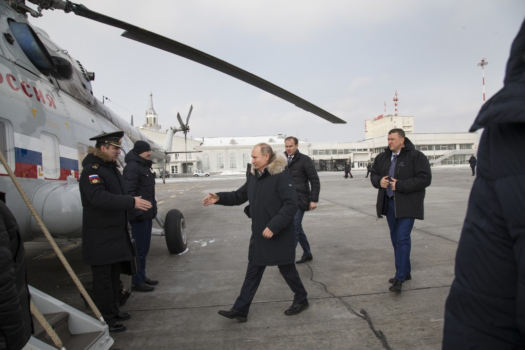 In this photo taken on Tuesday, March 6, 2018, Russian President Vladimir Putin, center, heads to a helicopter to fly to Nizhny Tagil shortly after ar