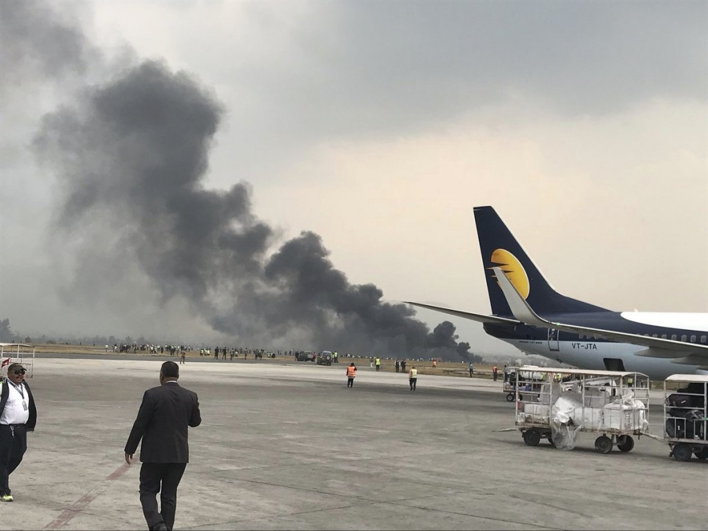 Smoke rises after a passenger plane from Bangladesh crashed at the airport in Kathmandu, Nepal, Monday, March 12, 2018. A passenger plane carrying 71
