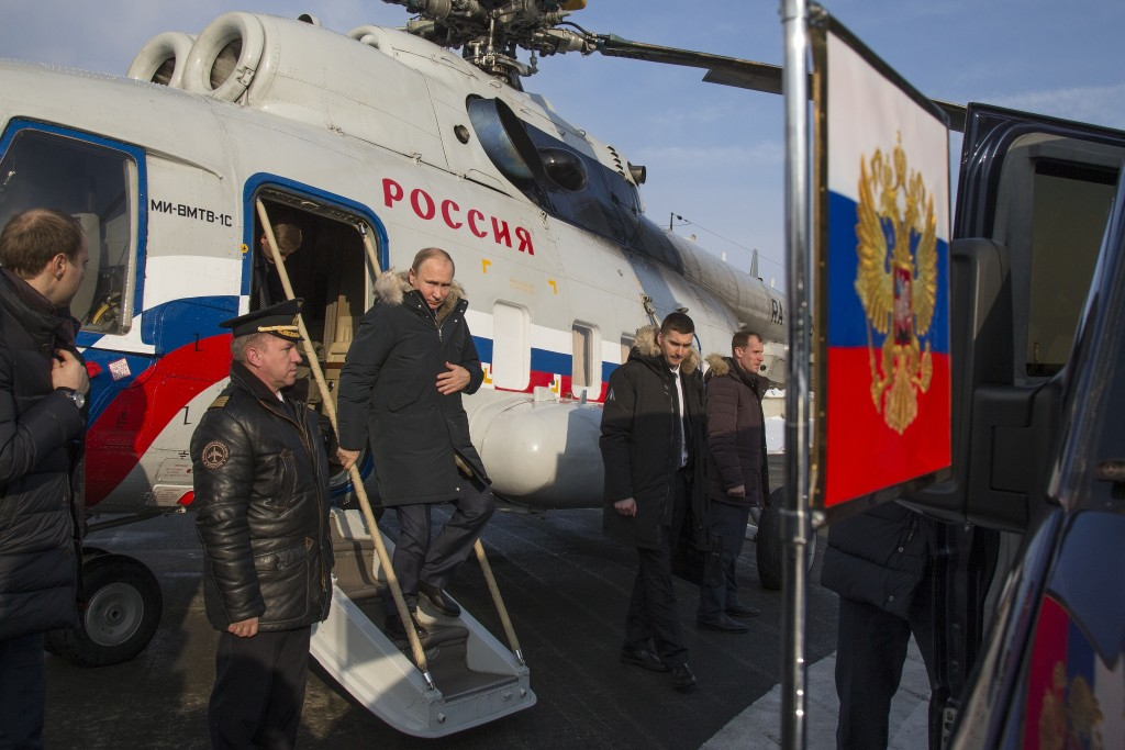 In this photo taken on Tuesday, March 6, 2018, Russian President Vladimir Putin, center, leaves Russian helicopter after landing to visit Uralvagonzav