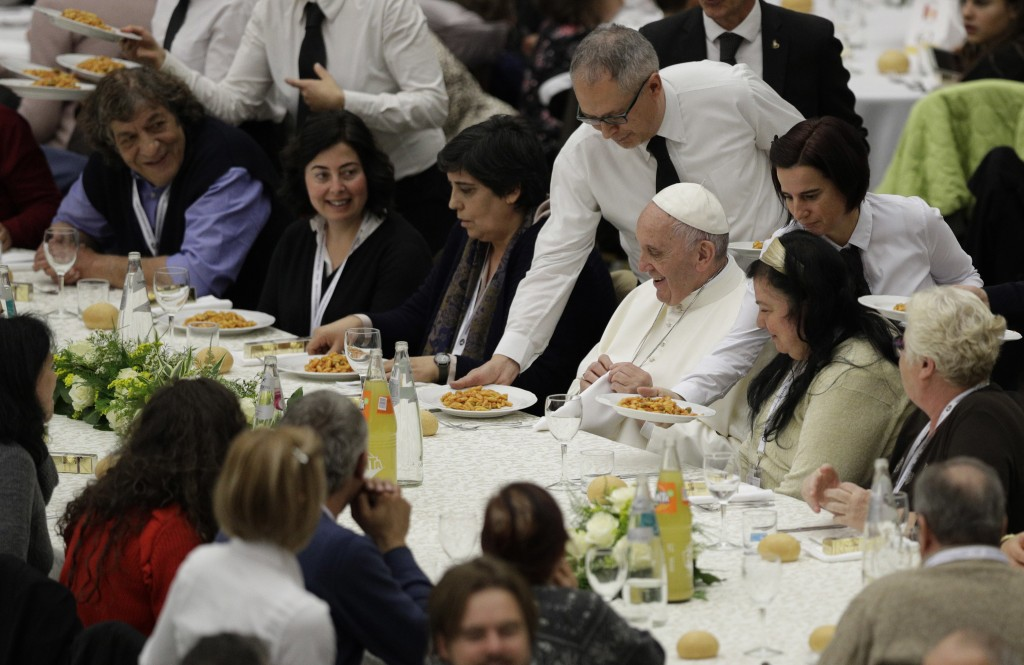 FILE - In this Nov. 19, 2017 file photo, Pope Francis is served gnocchetti during a lunch with several hundred poor people, at the Vatican on World Da