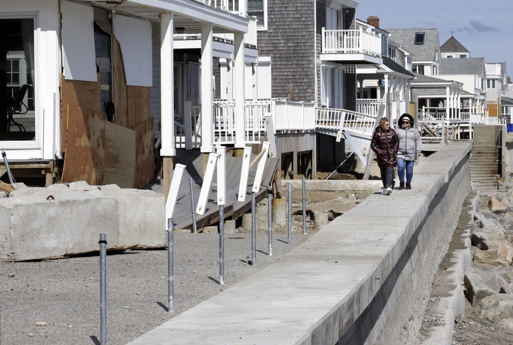 Maureen Niland, of Marshfield, Mass., left, and Kim Varghese, of Plymouth, Mass., right, walk along a seawall near damaged beachfront homes, Sunday, M
