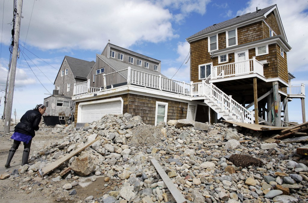 A passerby pauses near a pile of rocks, sand and debris near beachfront homes, Sunday, March 11, 2018, in Marshfield, Mass. The Northeast is bracing f