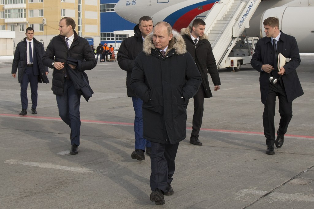 In this photo taken on Tuesday, March 6, 2018, Russian President Vladimir Putin, center, walks surrounded by aides and bodyguards upon his arrival to