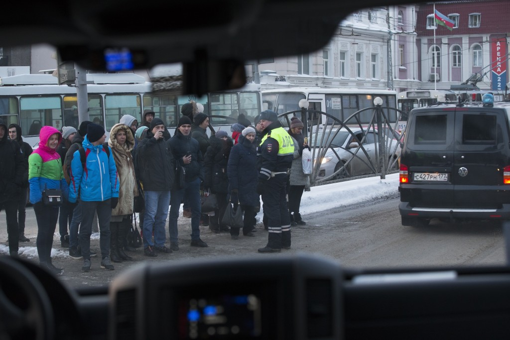 In this photo taken on Tuesday, March 6, 2018, through a motorcade's car window, local people watch at the motorcade carrying Russian President Vladim