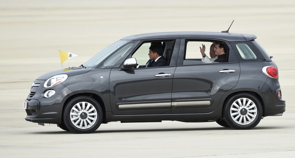 FILE - In this Sept. 22, 2015, file photo, Pope Francis waves from inside a Fiat 500 as he departs Andrews Air Force Base in Md. One of the two Fiats