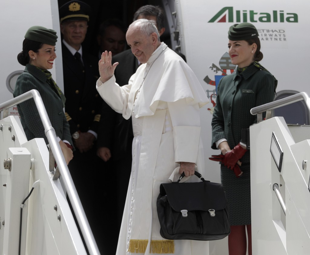 FILE - In this May 12, 2017 file photo, Pope Francis holds his bag and waves as he embarks his flight to Monte Real, Portugal, from Rome's Internation