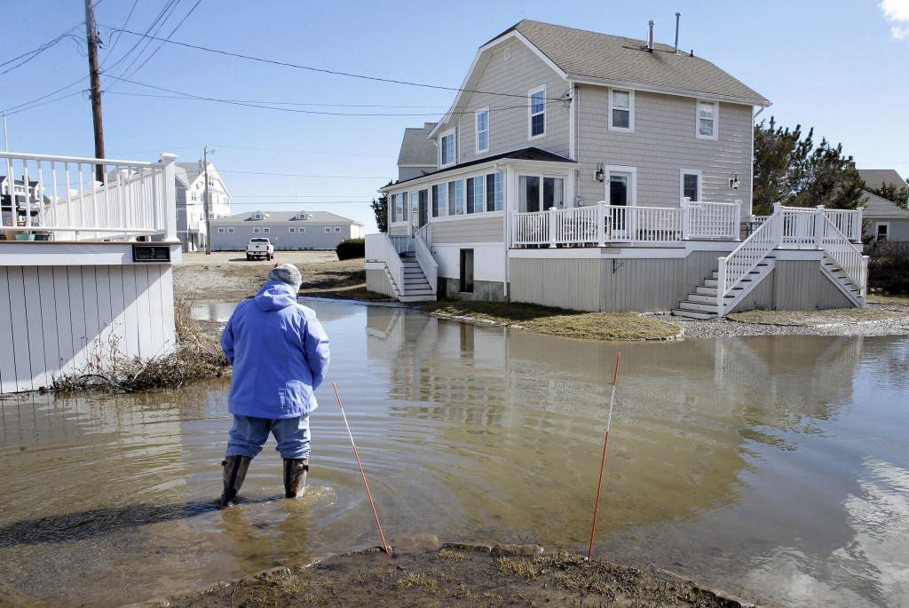 A resident of Duxbury, Mass., views flooding near her home, Sunday, March 11, 2018, in Duxbury. The Northeast is bracing for its third nor'easter in f