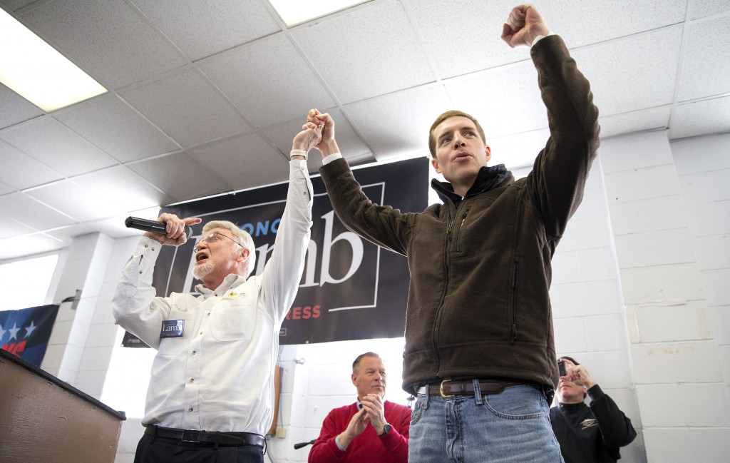 Cecil Roberts, president of the United Mine Workers, left, lifts up Democratic candidate Conor Lamb's hand as the crowd erupts in cheers and chants du