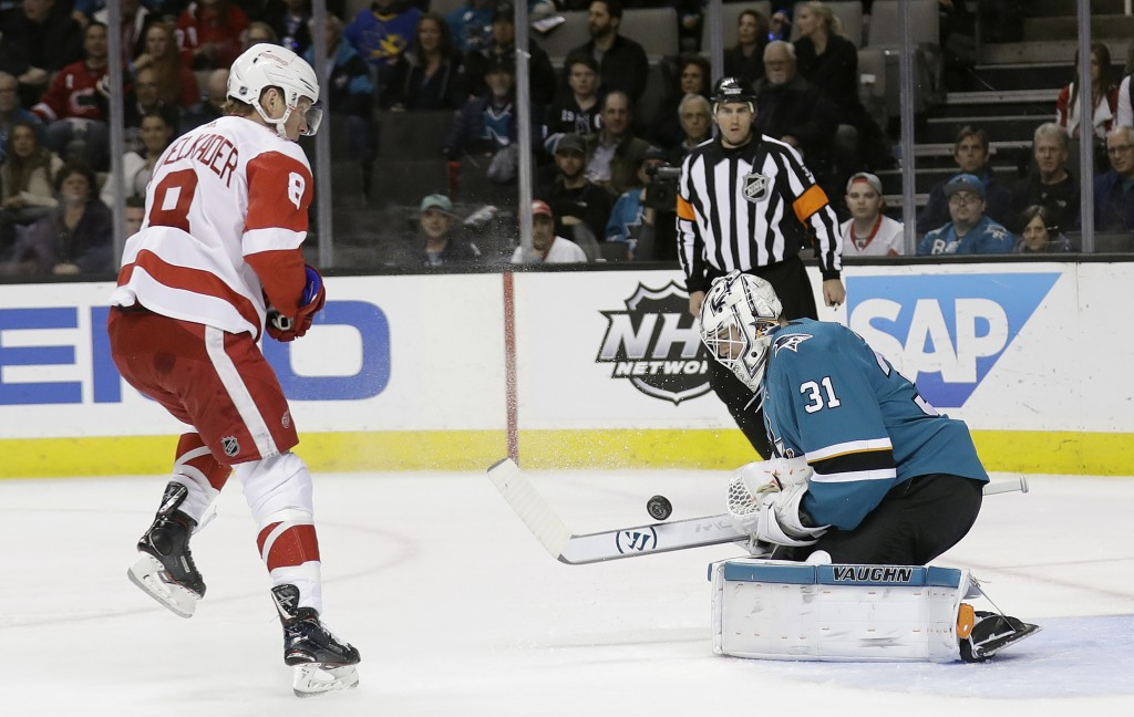 San Jose Sharks goaltender Martin Jones, right, stops a shot in front of Detroit Red Wings' Justin Abdelkader during the first period of an NHL hockey