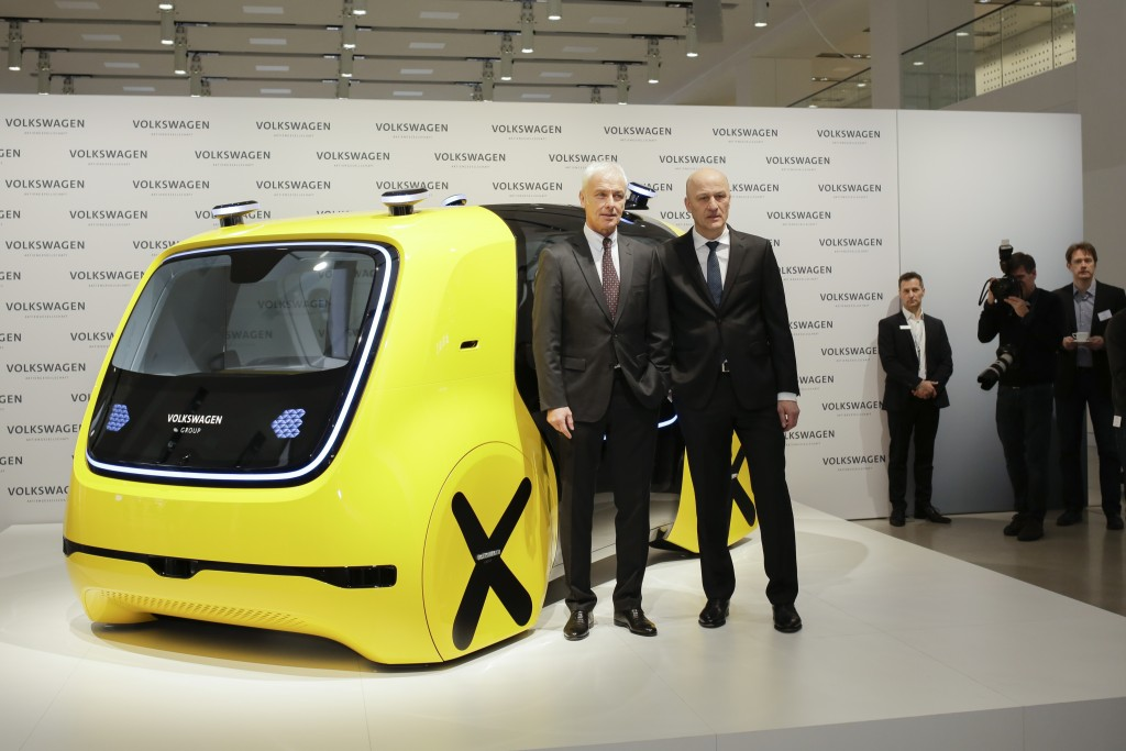VW group CEO Matthias Mueller, left, and CFO Frank Witter, right, pose in front of a self driving concept car prior to the annual media conference of
