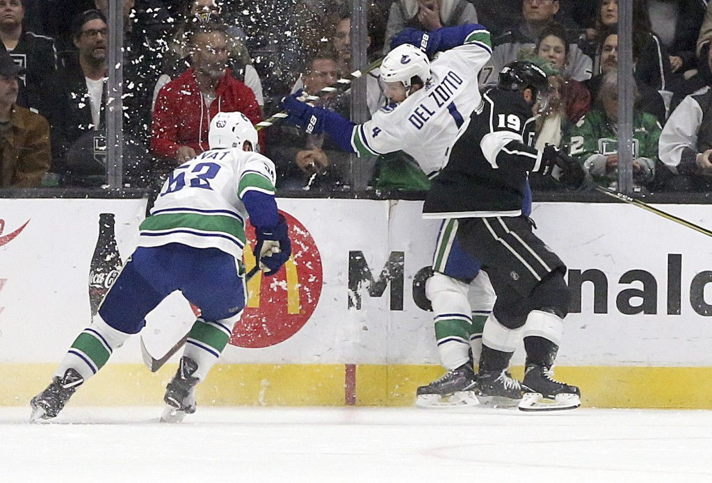Vancouver Canucks center Bo Horvat (53) and defenseman Michael Del Zotto (4) collide with Los Angeles Kings center Alex Iafallo (19) in the first peri