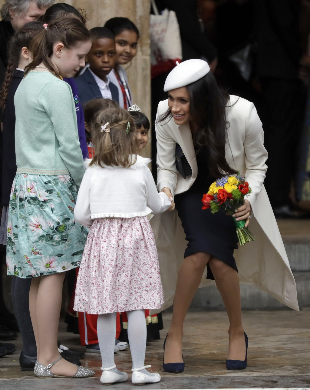 Meghan Markle receives flowers as she leaves after attending the Commonwealth Service at Westminster Abbey in London, Monday, March 12, 2018. Organise