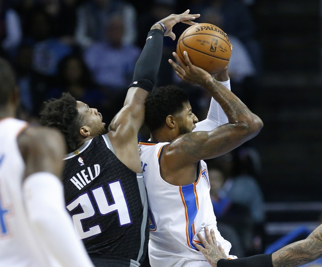 Oklahoma City Thunder forward Paul George, right, goes to the basket in front of Sacramento Kings guard Buddy Hield (24) in the first half of an NBA b