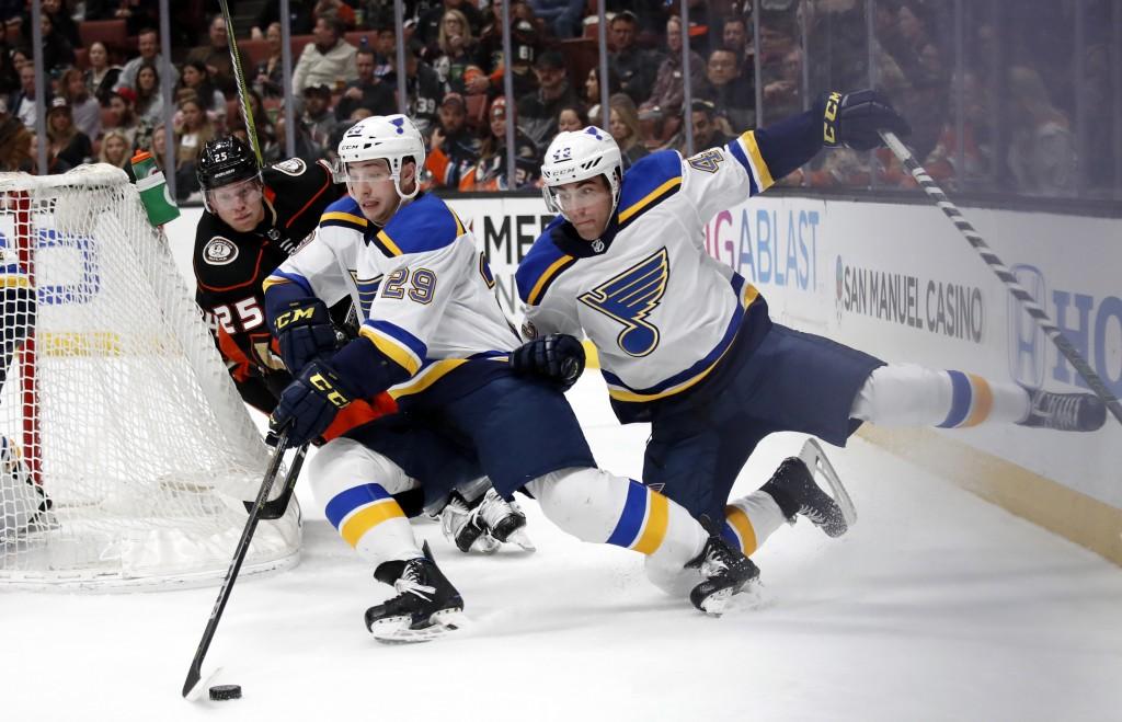 St. Louis Blues' Vince Dunn (29) collides with teammate Jordan Schmaltz, right, as he moves the puck past Anaheim Ducks' Ondrej Kase, of the Czech Rep