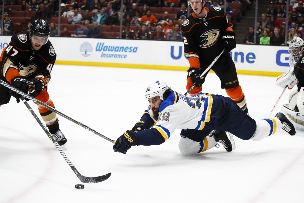 St. Louis Blues' Chris Thorburn, center, falls to the ice as he reaches for the puck against Anaheim Ducks' Hampus Lindholm, left, of Sweden, during t