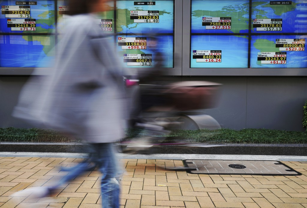 People walk past an electronic stock board showing Japan's Nikkei 225 index and other countries' indexes at a securities firm in Tokyo Tuesday, March