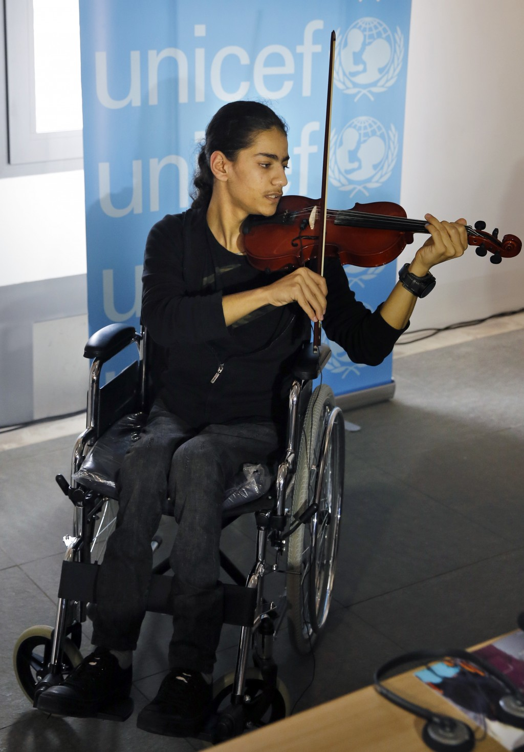 In this Monday, March 12, 2018 photo, Bassel Mokdad, 17, who is paralyzed from a spinal injury he incurred during the war in Syria, plays a violin dur