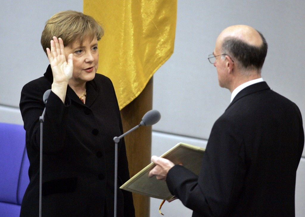 FILE - In this Nov. 22, 2005 file photo newly appointed German chancellor Angela Merkel, left, takes the oath of office in the parliament in Berlin. A