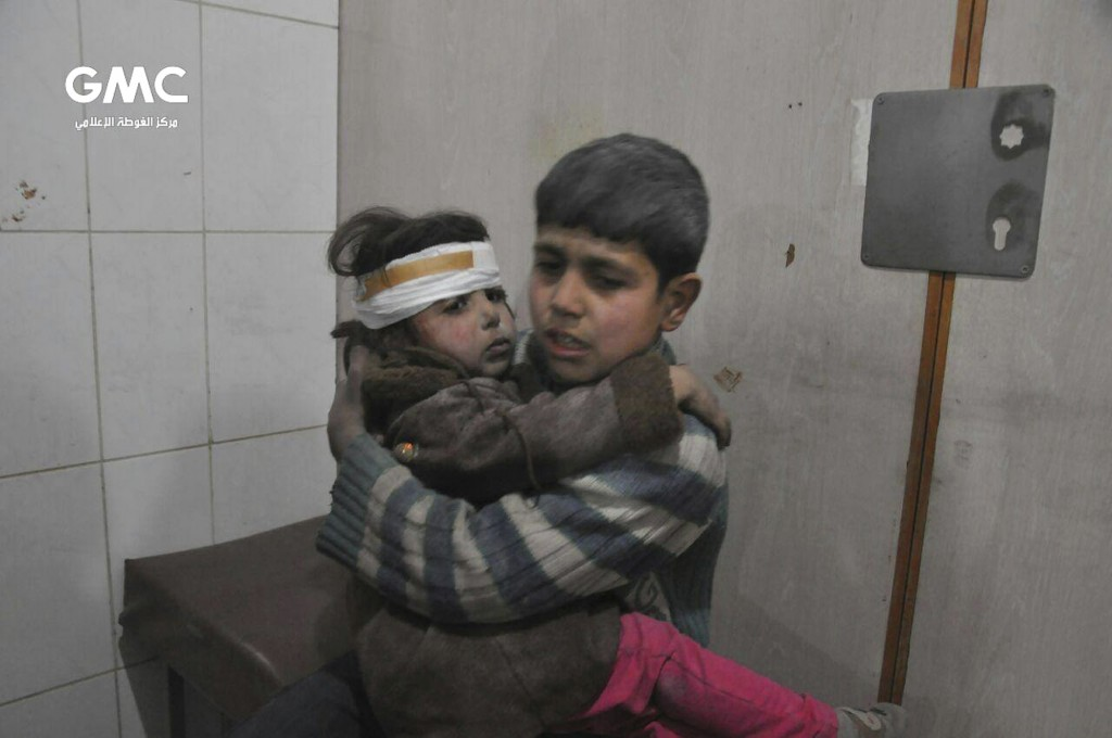 FILE - This file photo released Feb. 21, 2018 provided by the Syrian anti-government activist group Ghouta Media Center, shows two Syrian children who