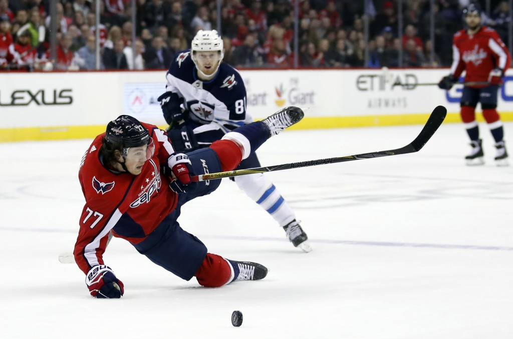 Washington Capitals right wing T.J. Oshie (77) falls to the ice with Winnipeg Jets left wing Kyle Connor (81) behind in the first period of an NHL hoc