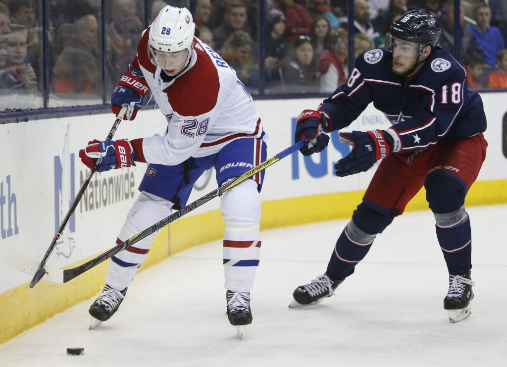 Montreal Canadiens' Mike Reilly, left, clears the puck as Columbus Blue Jackets' Pierre-Luc Dubois defends during the second period of an NHL hockey g