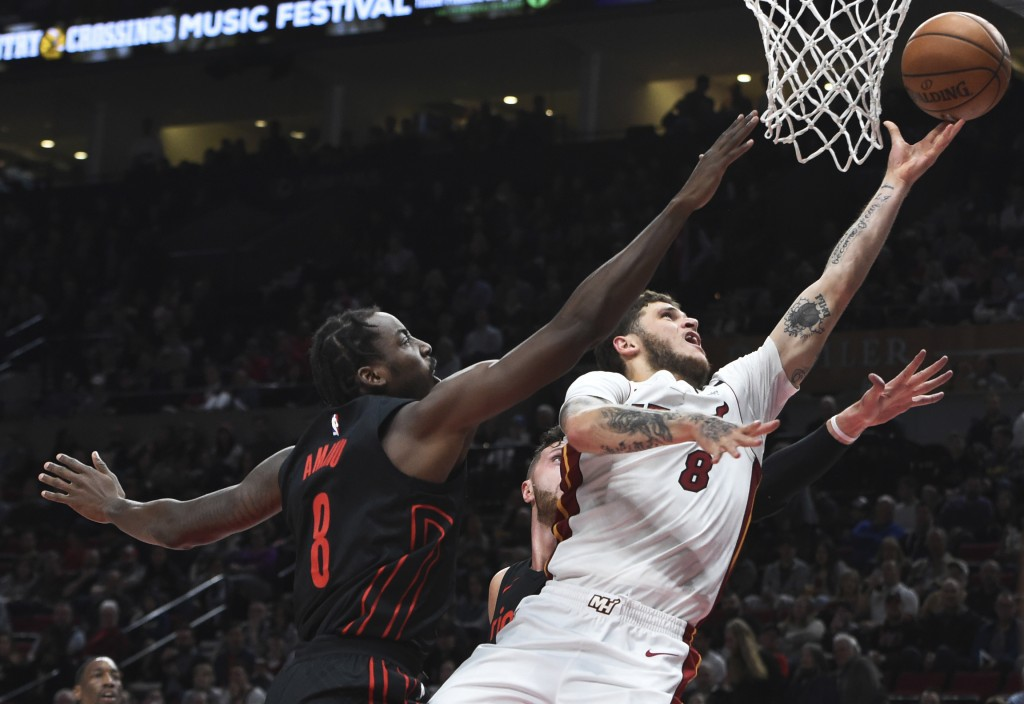 Miami Heat guard Tyler Johnson (8) drives to the basket on Portland Trail Blazers forward Al-Farouq Aminu during the first half of an NBA basketball g