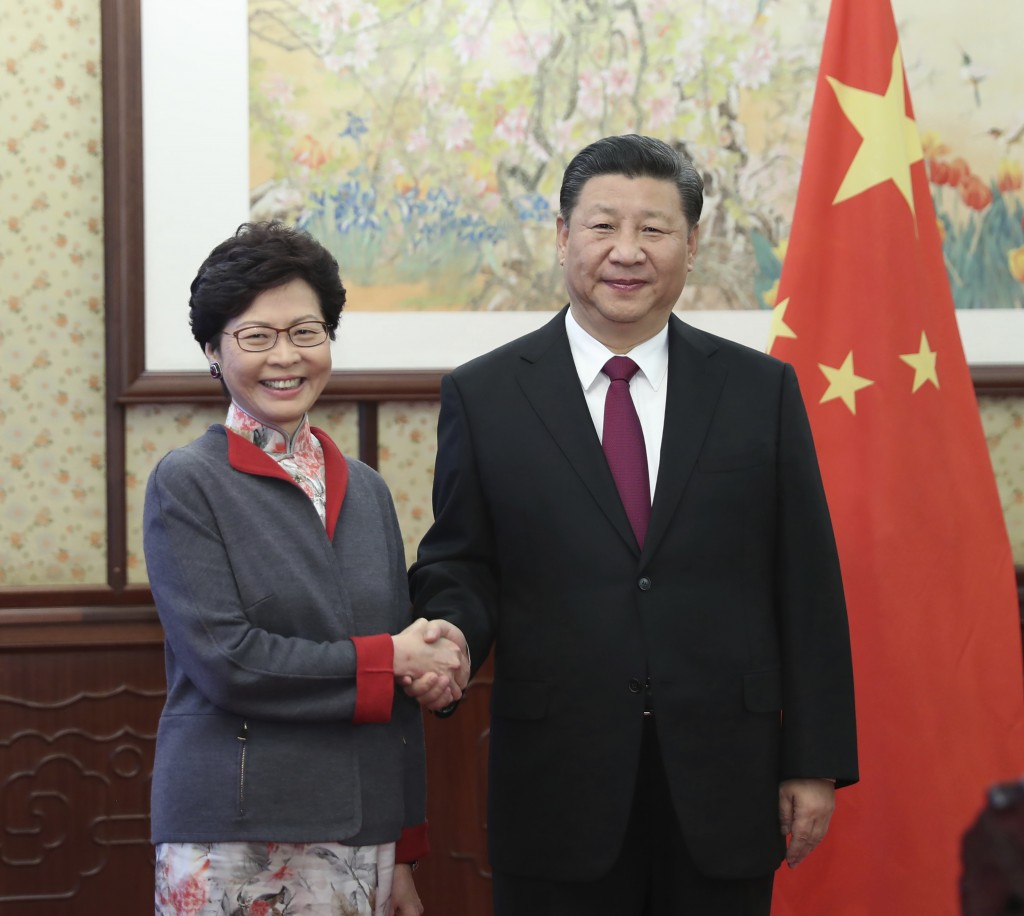 FILE - In this Dec. 15, 2017, file photo released by China's Xinhua News Agency, Hong Kong Chief Executive Carrie Lam, left, poses with Chinese Presid