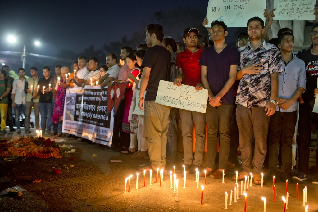 Bangladeshi and Nepali people light candles to pay homage to the victims of Monday's plane crash in Kathmandu, as they gather at the Dhaka University